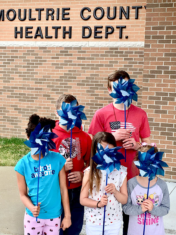 children holding blue pinwheels in front of their faces for Child Abuse Awareness Month