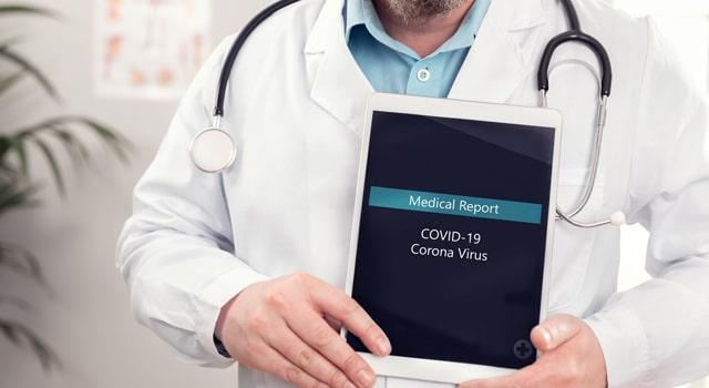 Doctor holding an Ipad with coronavirus report