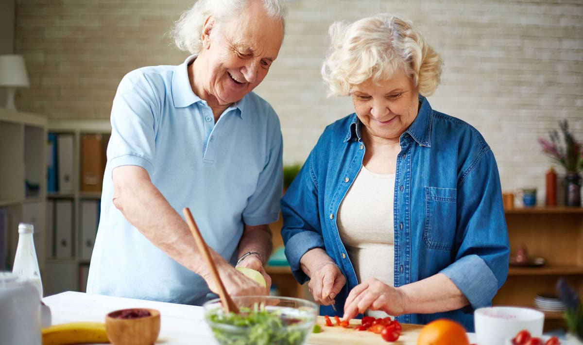 Older couple making a salad together