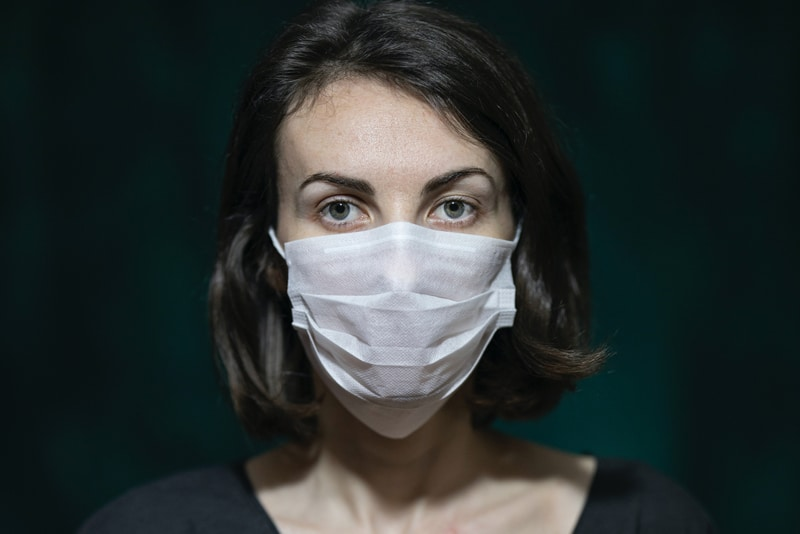 Woman wearing a facemask staring into camera.